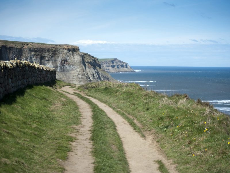 Cleveland Way track running along the top of the headland on the North Yorkshire coast overlooking the ocean on a sunny day